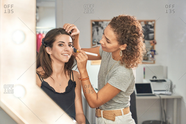Concentrated makeup artist doing makeup on a beautiful woman client in a salon