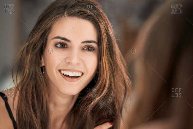 Reflection of charming long haired woman in mirror after cosmetic procedure in salon