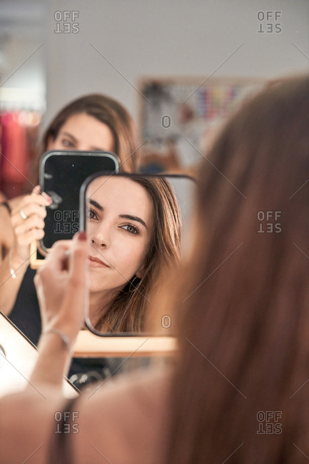 Reflection of a beautiful woman face in mirror in hand of smiling lady after cosmetic procedure in salon