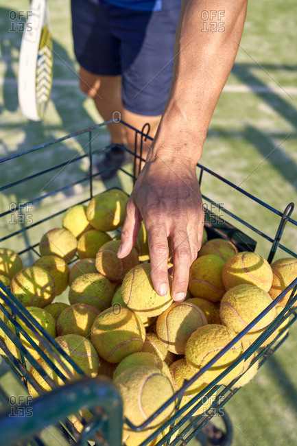 From above anonymous man picking yellow ball from basket while playing paddle tennis on court