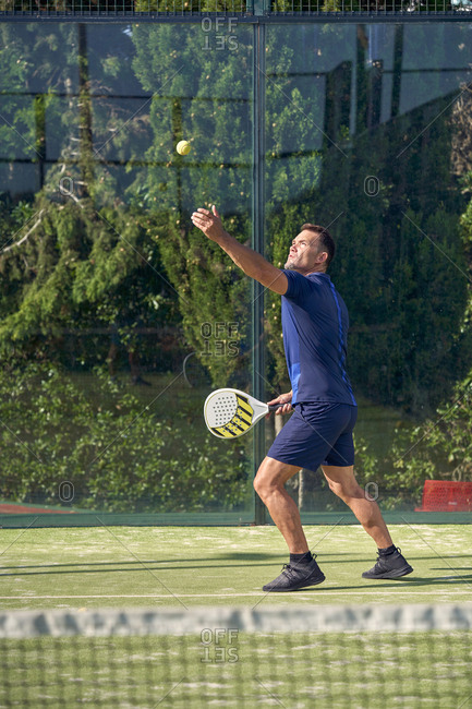 Adult man in sportswear playing paddle tennis on sunny day on court