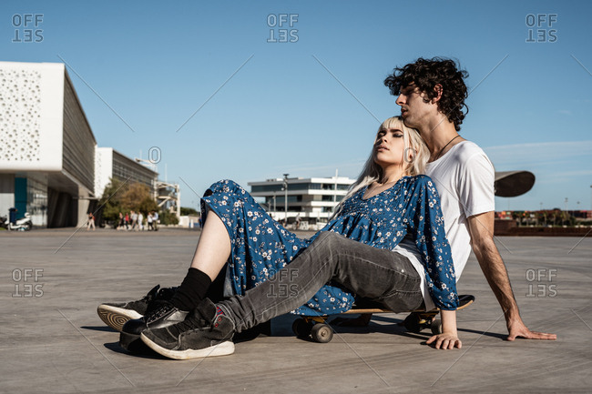 Attractive sensual blond woman with closed eyes lying on man sitting on skateboard and dreaming against blue sky and blurred modern buildings on square