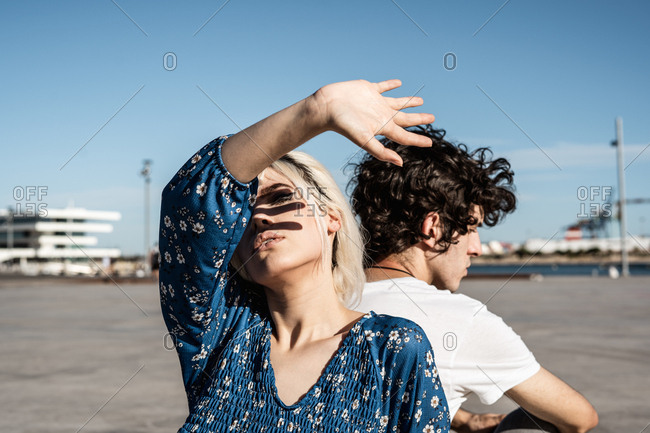 Attractive pensive woman covering herself from the sun while sitting back to back with young man and dreaming against blue sky and blurred modern buildings on square