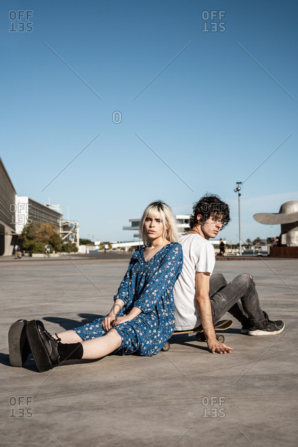 Attractive sensual blond woman looking at camera sitting with boyfriend on skateboard and dreaming against blue sky and blurred modern buildings on square