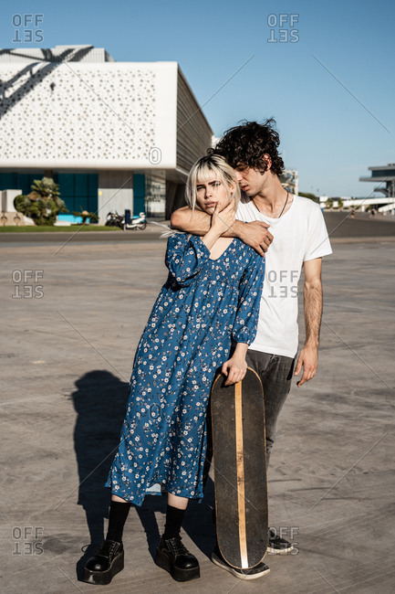 Young trendy loving couple standing and leaning on skateboard on square against blue sky and blurred modern buildings in windy weather