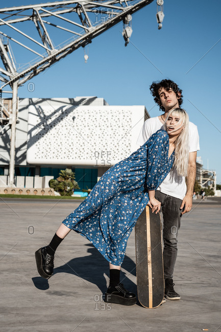 Pretty blond looking away with curiosity while leaning on skateboard beside modest exhausted man on square against blue sky and blurred modern buildings in windy weather