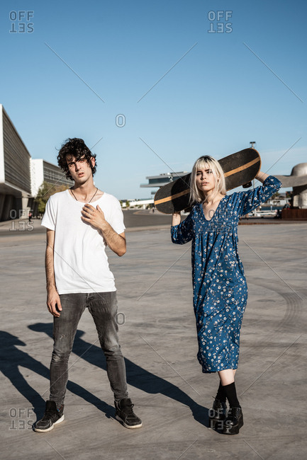 Young trendy loving couple standing while woman holds a skateboard on square against blue sky and blurred modern buildings in windy weather