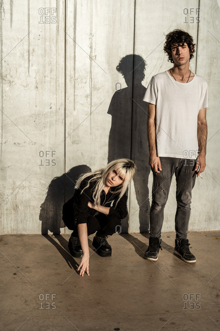 Charismatic blond provocative female in black clothes and shoes crouched beside tall relaxed man with cigarette standing and looking at camera with interest against gray cement wall in sunny day
