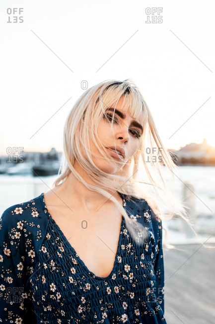 Gorgeous pensive blond female with black eyebrows in blue oversize dress looking at camera with curiosity while standing and touching hair on street during sunset
