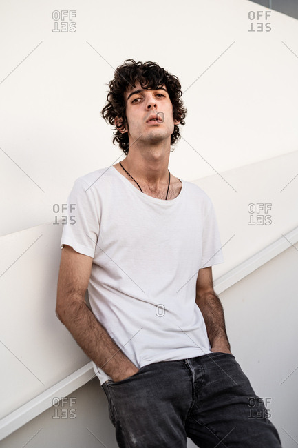 From below handsome confident dark haired man in casual clothes looking at camera against white wall