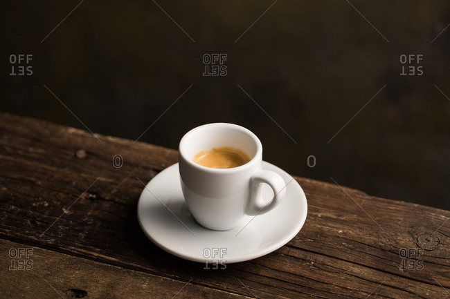 From above delicious fragrant brown beverage with white foam in ceramic cup on wooden table