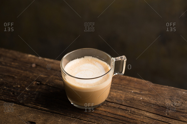 From above delicious fragrant brown beverage with white foam in glass cup on wooden table