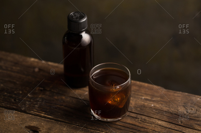 From above delicious fragrant brown beverage in a glass on wooden table
