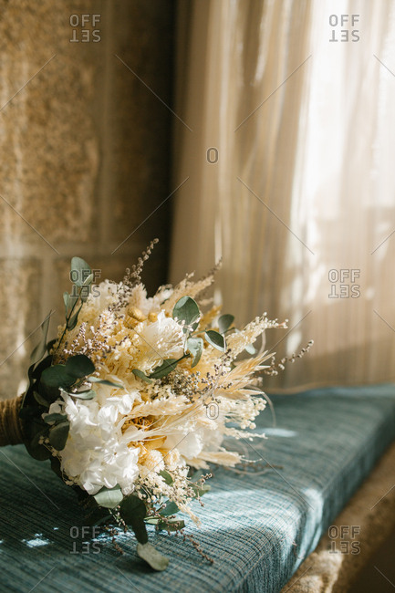 Bunch of delicate white flowers placed on blue rustic cushion near window at home