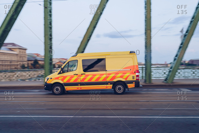 Side view of yellow compact van moving fast on empty road along metal bridge contraction in Budapest