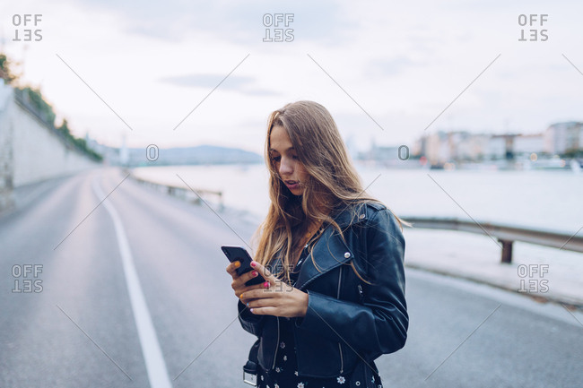 Long haired stylish woman browsing smartphone