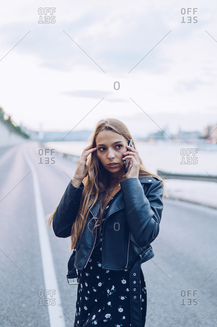 Long haired stylish woman speaking on smartphone