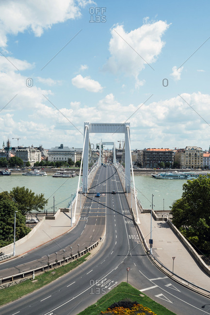 From above gray marked asphalt roads interconnecting with large bridge construction above calm river in cloudy day in Budapest