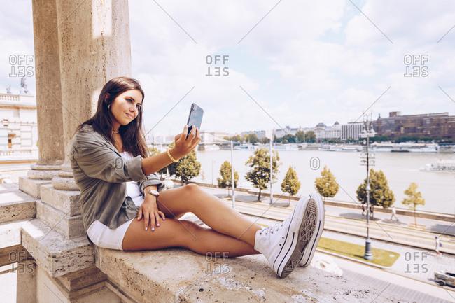 Woman taking selfie on old building