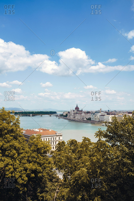Serene landscape of calm river floating along city with houses and gardens under bright cloudy sky in Budapest