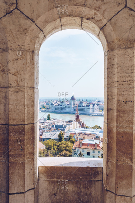 Ancient shabby window overlooking picturesque landscape on city and calm river under bright sky in Budapest
