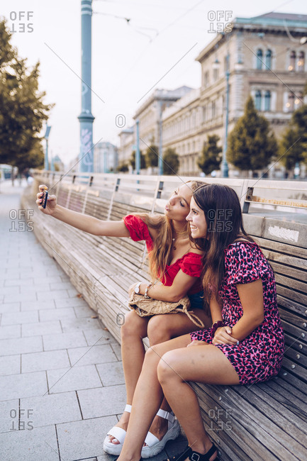 Active smiling women in in colorful dress taking selfie comfortable placed on long wooden bench on background of ancient building in Budapest