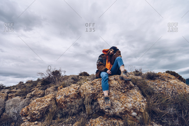 From below positive woman looking at camera and sitting on rock at edge of cliff with picturesque view