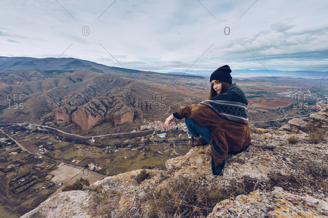From above positive woman looking at camera and sitting on rock at edge of cliff with picturesque view