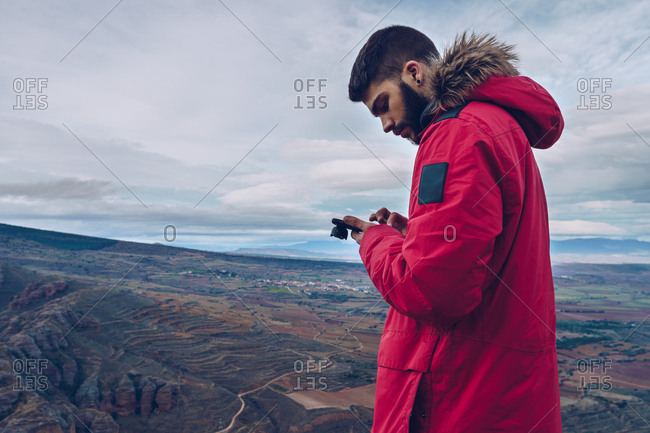 Side view of attentive man in jacket using smartphone while standing at cliff over breathtaking view