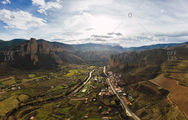 Drone view of scenic grassy mountain slopes and fields with infrastructure in valley