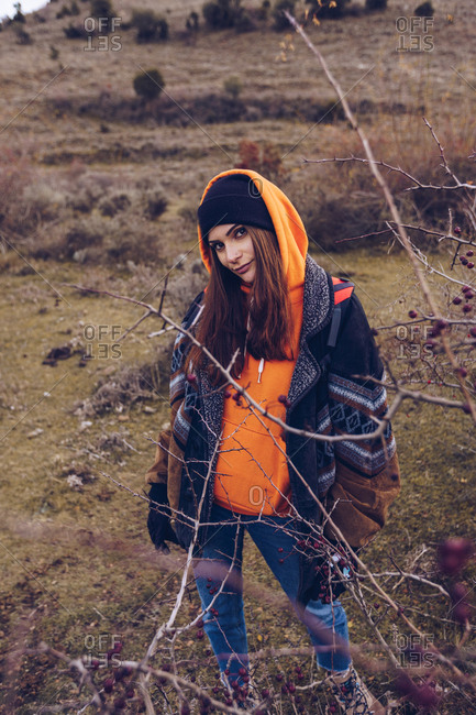 Young woman with bright backpack in warm clothes standing on field with dried leaves by bare trees on cloudy day and looking at camera