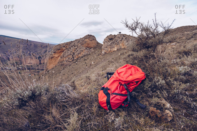 Colorful red backpack on dried grass at rocky hill on cold autumn day