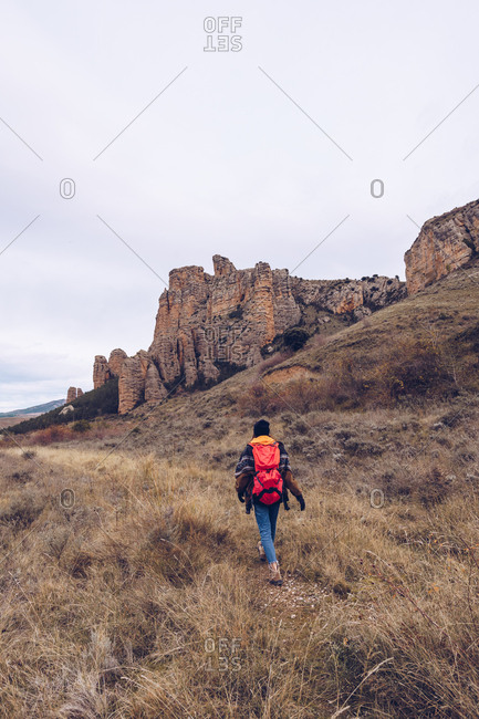 From behind person with bright backpack in warm clothes walking along concrete pathway at field with bare trees and distant tall mountain on cloudy day