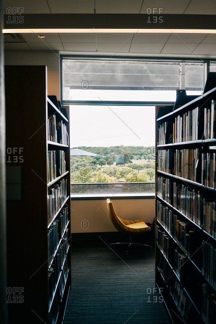 Bookshelves in room with comfortable chair nearby window in library of Texas