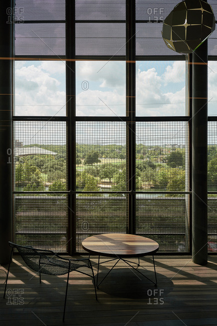 Lounge area with round wooden table and metal chair against tall windows with grid in contrast light in library Texas