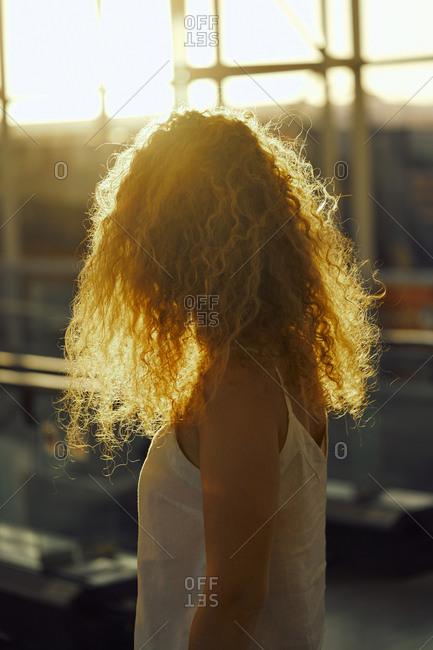 Curly charming woman smiling away while walking in light glassy room of airport in Texas