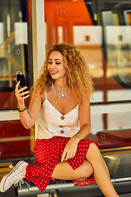 Pleasant cheerful woman in earphones listening to music with mobile phone while chilling on metal bench in airport of Texas