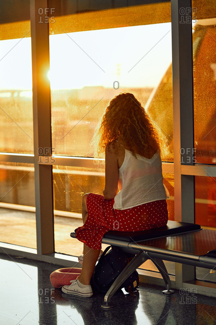 Stylish cheerful woman sitting on metal bench in glass hallway of airport in Texas