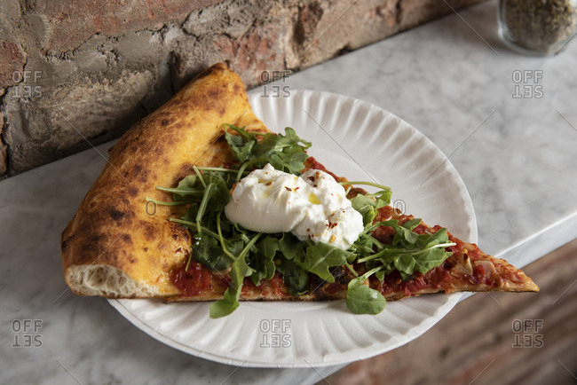 Slice of pizza with arugula and ricotta