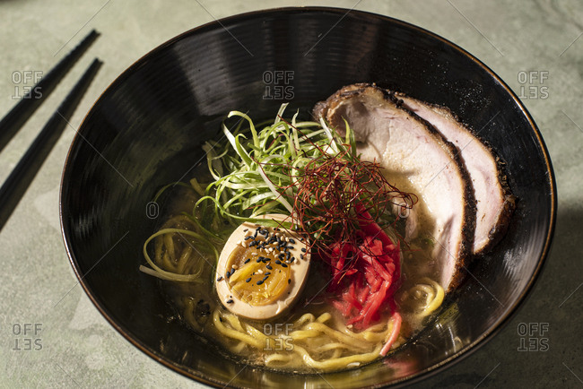 Bowl of ramen with meat and egg on green table with chopsticks