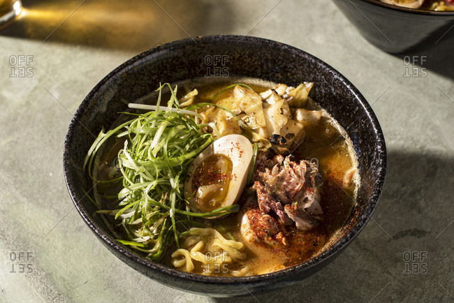 Bowl of ramen with meat and egg on green table
