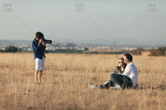 Photographer taking portrait of a pregnant couple in a field
