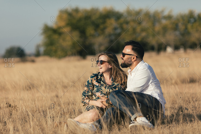 Portrait of a pregnant couple sitting in a field