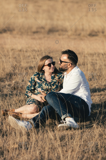 Happy pregnant couple sitting in a field