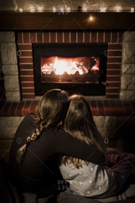 Rear view of mother and daughter snuggling by a fire