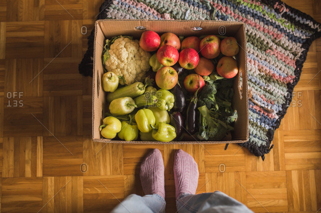First person perspective view looking down at a box filled with fresh produce