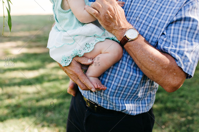 Mid-section of father holding his barefoot baby girl
