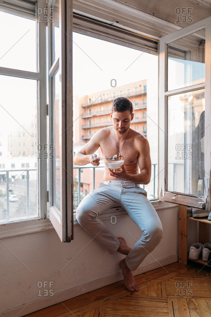 Shirtless young man sitting on an open window, having a breakfast