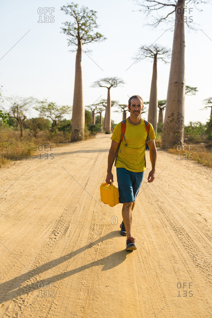 Man walking in the Avenue of the Baobabs carrying a yellow case, Morondava, Madagascar