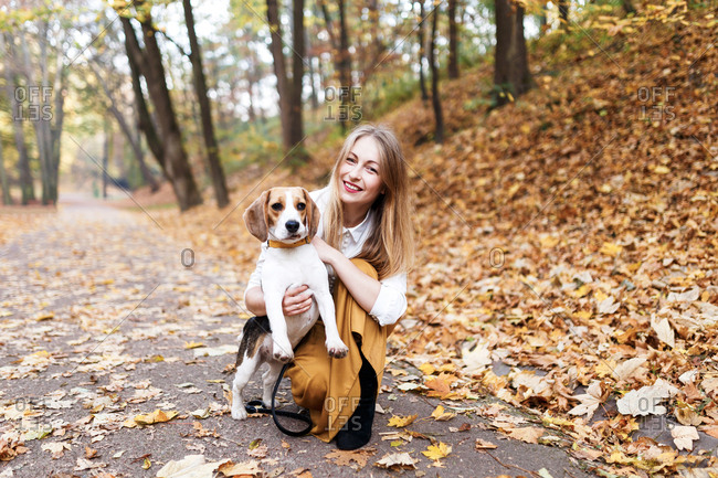 The woman teaches the beagle puppy commands while walking at the park and hugging